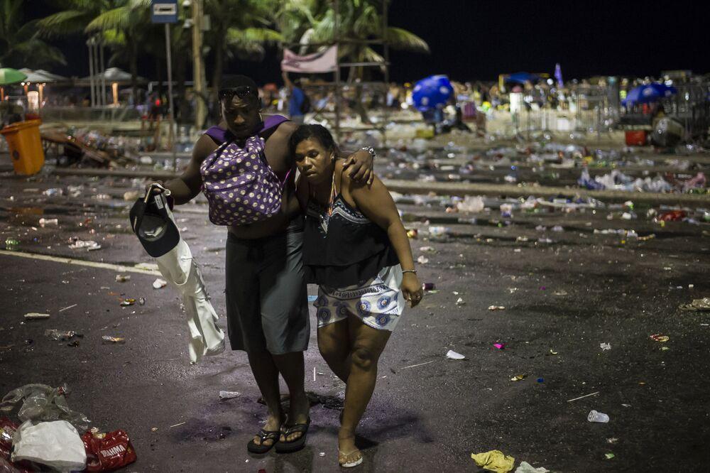 Mulher recebe ajuda após confrontos entre policiais e foliões após o início oficial do carnaval na praia de Copacabana, no Rio de Janeiro