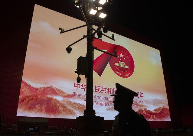 Um agente de segurança passa por câmeras de vigilância em Pequim, perto de uma tela do 70º aniversário da fundação da República Popular da China