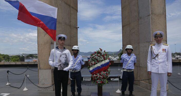 Marinheiros russos posam com retrato de soldado morto durante a Segunda Guerra Mundial junto à chama do soldado desconhecido