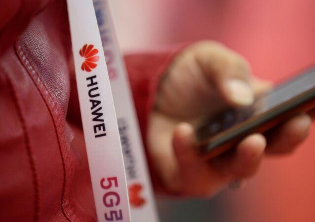 Um participante usa uma faixa de crachá com o logotipo da Huawei de participante na Exposição Mundial 5G em Pequim
