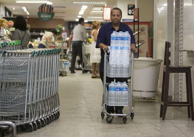 Homem compra água mineral em supermercado em Copacabana, Rio de Janeiro. Residentes do Rio estão preocupados com a qualidade da água.