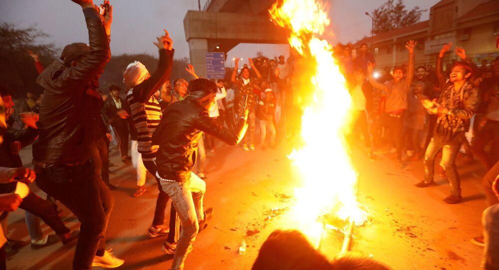 Manifestantes queimam uma efígie representando o primeiro-ministro Narendra Modi durante um protesto contra uma nova lei de cidadania, perto da Universidade Jamia Millia Islamia, em Nova Deli, Índia, em 16 de dezembro de 2019