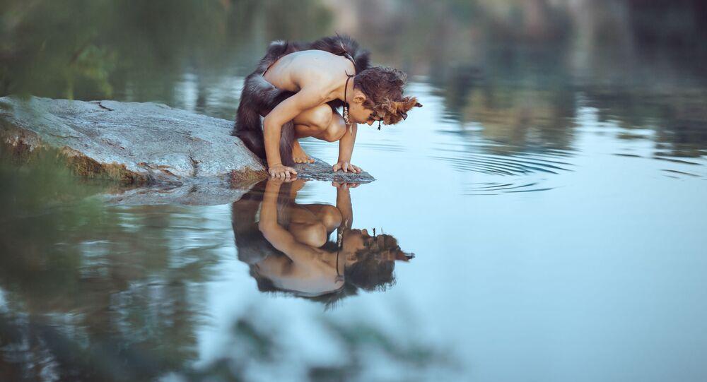Menino da época dos homens das cavernas sentado na rocha e olhando para o seu próprio reflexo na água do lago. Conceito de sobrevivência de evolução. Foto de arte criativa