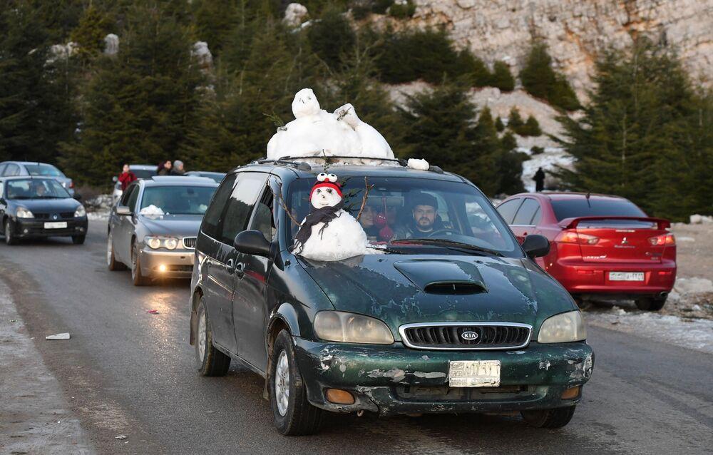 Sírios trazem neve das montanhas em um carro na província síria de Latakia