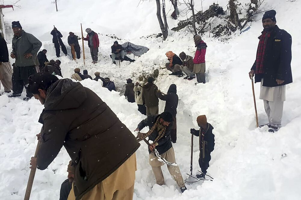 Moradores locais procuram vítimas de avalanche na neve, em Caxemira controlada pelo Paquistão