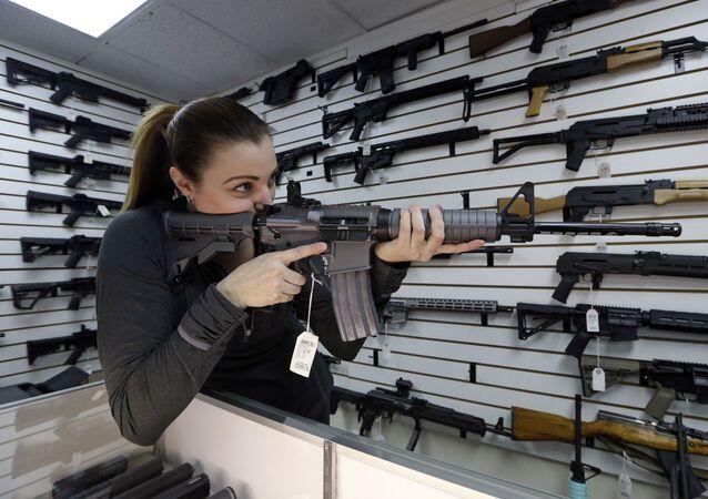 Dona de loja de armas, Tiffany Teasdale-Causer, aponta um fuzil AR-15 semiautomático, o mesmo usado para realizar massacre em igreja no Texas, em novembro de 2017