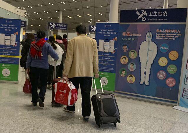 Passageiros passagem por controle de saúde antes de embarcar no Aeroporto Internacional de Pequim