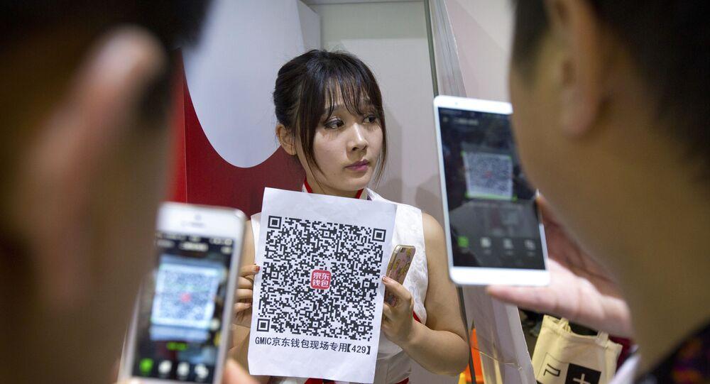 Chineses escaneiam código QR pelo celular. Tecnologia blockchain, associada ao código QR, pode fornecer soluções ao comércio intra-BRICS