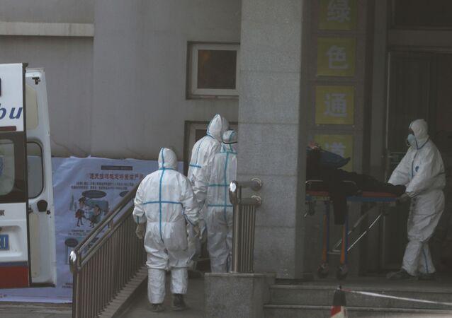 Médicos transferem paciente da ambulância para o hospital, onde os pacientes com pneumonia causada pelo coronavírus estão sendo tratados, em Wuhan, China, 20 de janeiro de 2020