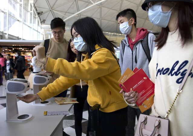 Viajantes higienizam suas mãos no Aeroporto de Hong Kong para evitar contaminações pelo coronavírus da China