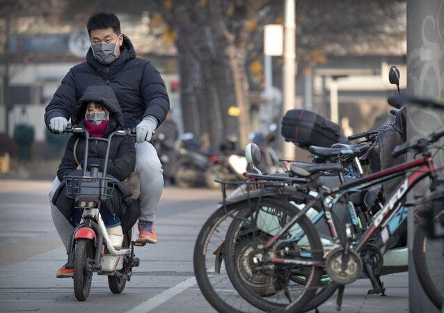 Casal usa máscaras para se proteger do novo coronavírus enquanto passeia de moto em Pequim
