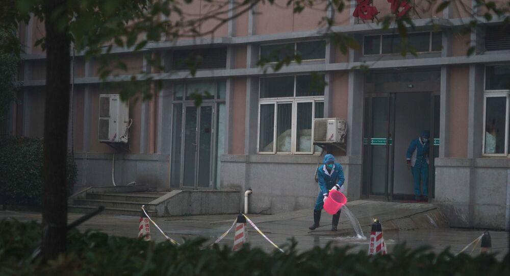 Funcionários do hospital lavam a entrada de emergência do Centro de Tratamento Médico de Wuhan, onde alguns infectados com um novo vírus estão sendo tratados, em Wuhan, China, quarta-feira, 22 de janeiro de 2020.