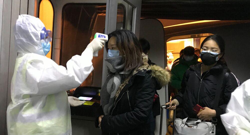 Agentes de saúde checam a temperatura de passageiros que chegam da cidade chinesa de Wuhan no aeroporto de Pequim no dia 22 de janeiro de 2020.