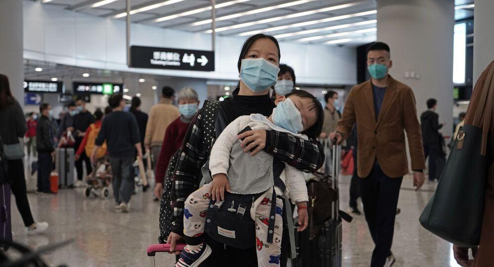 Mãe e filho caminham em aeroporto com máscaras para se proteger do novo coronavírus da China