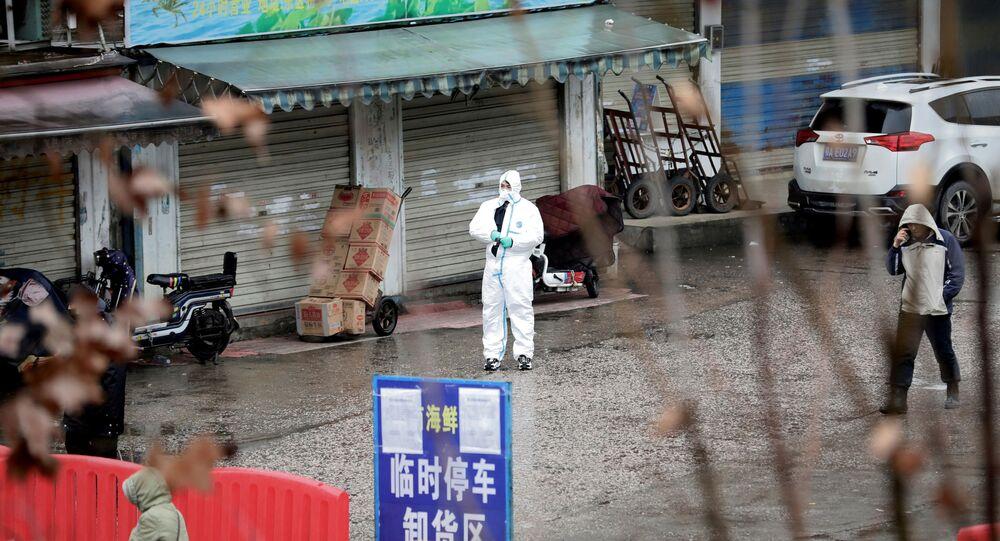 Um trabalhador de traje protector é visto no mercado de mariscos fechado em Wuhan, China