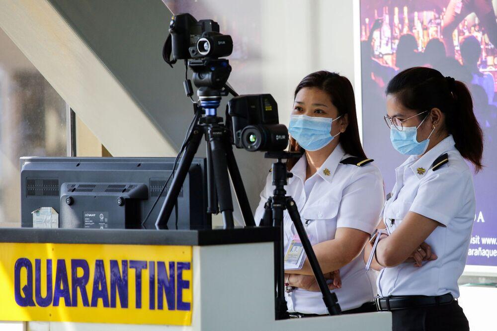 Funcionárias escaneiam passageiros no Aeroporto Internacional Ninoy Aquino, nas Filipinas