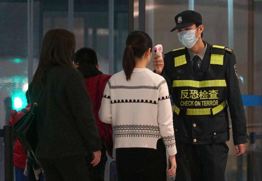 Passageiras passam por controle térmico no Aeroporto Internacional Tianhe, em Wuhan, China