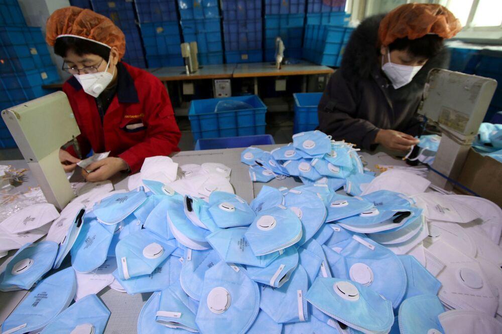 Trabalhadores produzindo máscaras em fábrica chinesa
