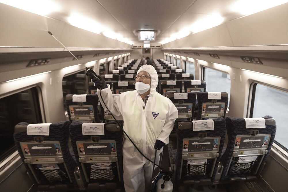 Funcionário realiza limpeza de trem como proteção contra coronavírus em estação ferroviária sul-coreana