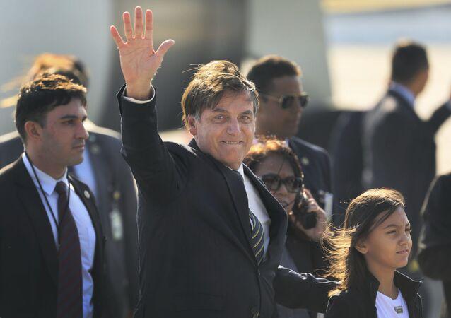 Bolsonaro acena ao chegar no aeroporto de Nova Deli, na Índia.