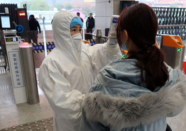 Funcionária do aeroporto de Xianning checa a temperatura de passageiro que desembarca na cidade.