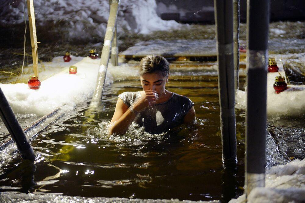 Mulher toma banho em cidade russa durante celebrações da Epifania do Senhor