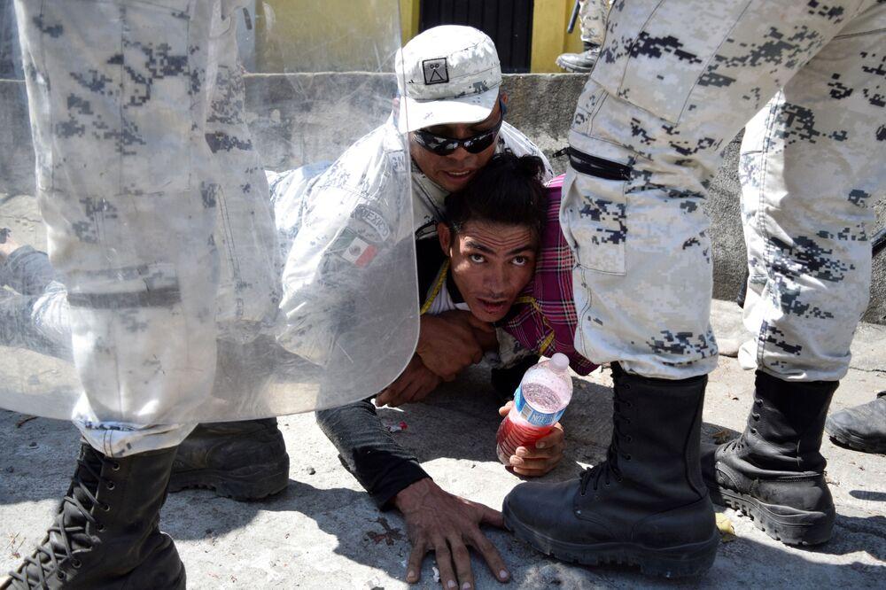 Membro da Guarda Nacional do México prende um imigrante, que tentava atravessar fronteira rumo aos EUA