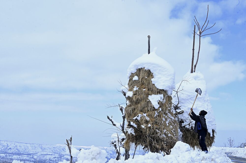 Camponês remove neve depois de forte nevasca na Índia