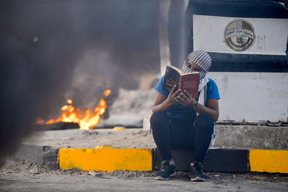 Manifestante lê romance sentado próximo de pneus queimados durante manifestação no Iraque