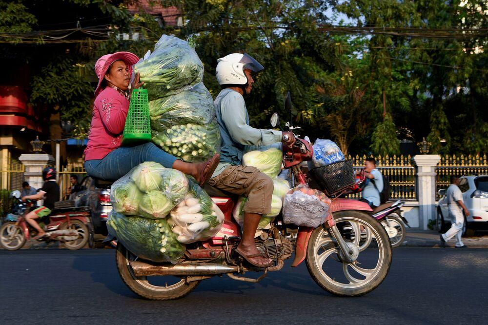 Mulher transporta vegetais empilhados em moto no Camboja