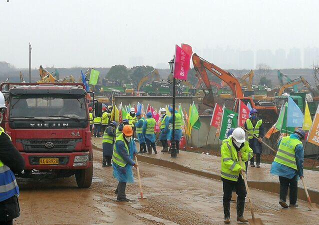 Operários limpam caminho durante a construção do novo hospital para tratar pacientes infectados pelo novo tipo de coronavírus, nos arredores da cidade de Wuhan, China, 24 de janeiro de 2020