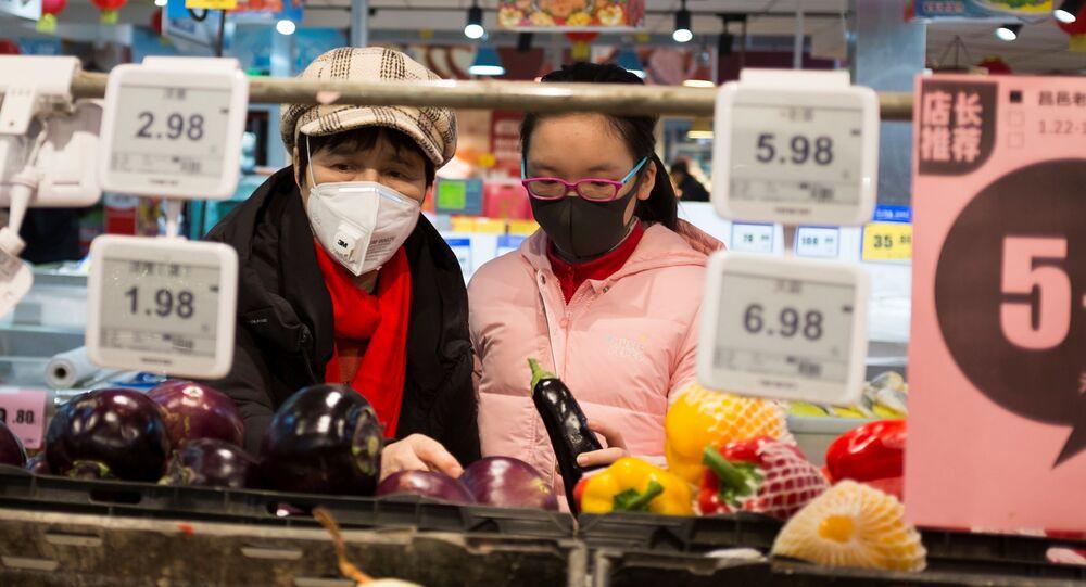 Consumidoras usam máscaras em supermercado de Pequim devido ao coronavírus, 25 de janeiro de 2020