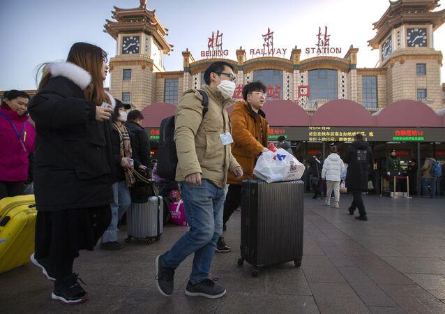 Viajante usando uma máscara facial enquanto caminha fora da estação de trem de Pequim, em Pequim, 20 de janeiro de 2020