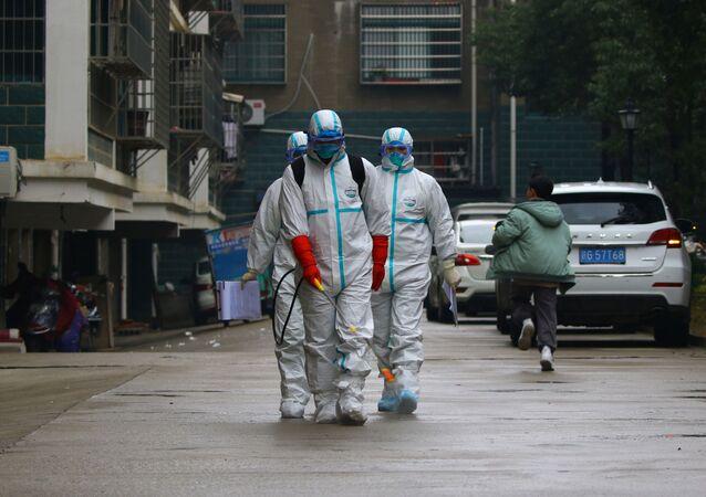 Trabalhadores do departamento local de controle e prevenção de doenças desinfectam área residencial após surto de coronavírus na província de Jiangxi, China, 25 de janeiro de 2020