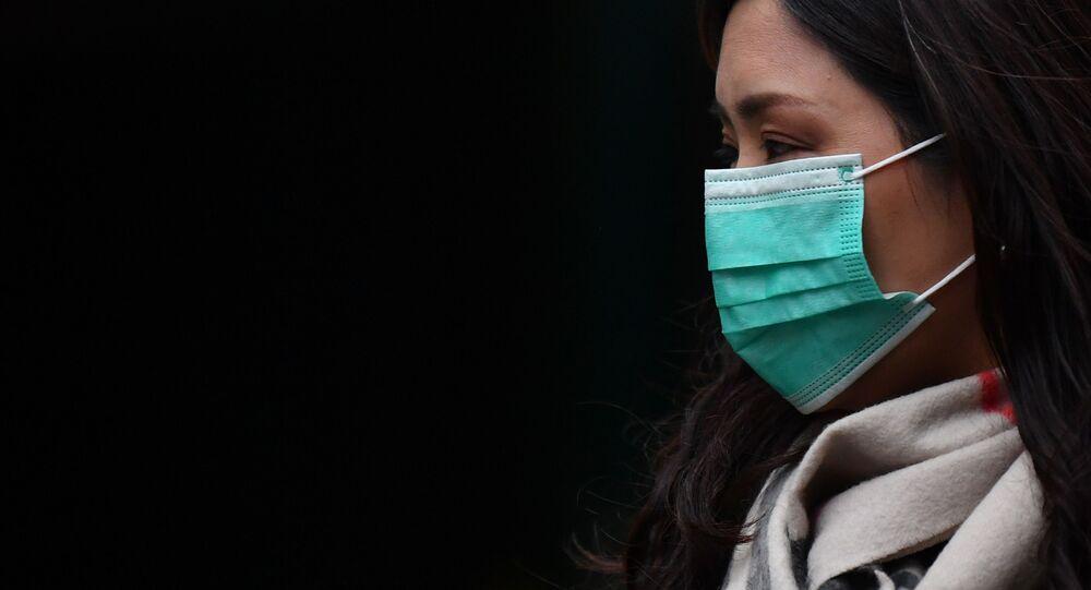 Uma pedestre usa uma máscara cirúrgica na Chinatown de Londres, em 24 de janeiro de 2020