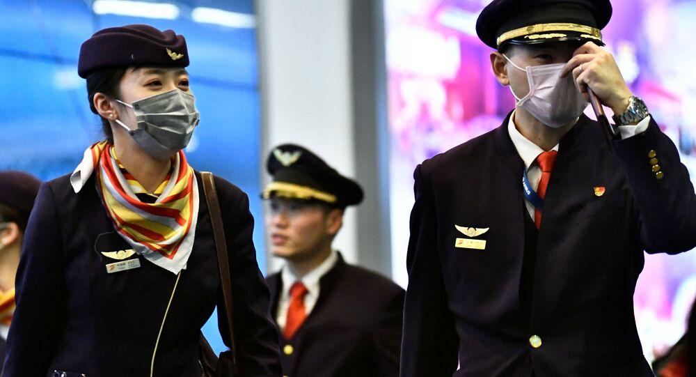 Tripulação de voo usa máscaras como proteção contra coronavírus em um voo direto da China para o Canadá, no Aeroporto Internacional de Vancouver, Canadá, em 24 de janeiro de 2020