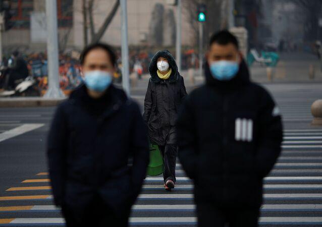Pessoas usando máscaras atravessam uma rua na China enquanto o país é atingido por um surto do novo coronavírus, em Pequim, 28 de janeiro de 2020