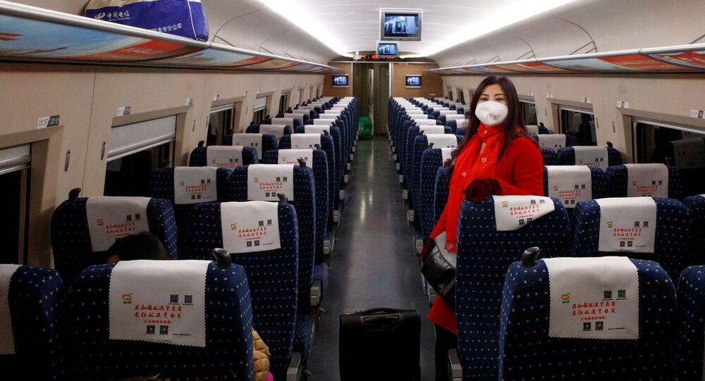 Uma mulher usa uma máscara enquanto viaja em um trem de alta velocidade perto de Jiujiang, na província de Jianxi, em meio ao surto de coronavírus na China.