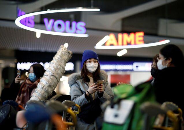 Passageiros de voo da Air China de Pequim usam máscaras