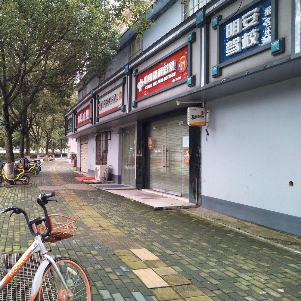 Rua deserta com lojas fechadas na cidade de Wuhan, China