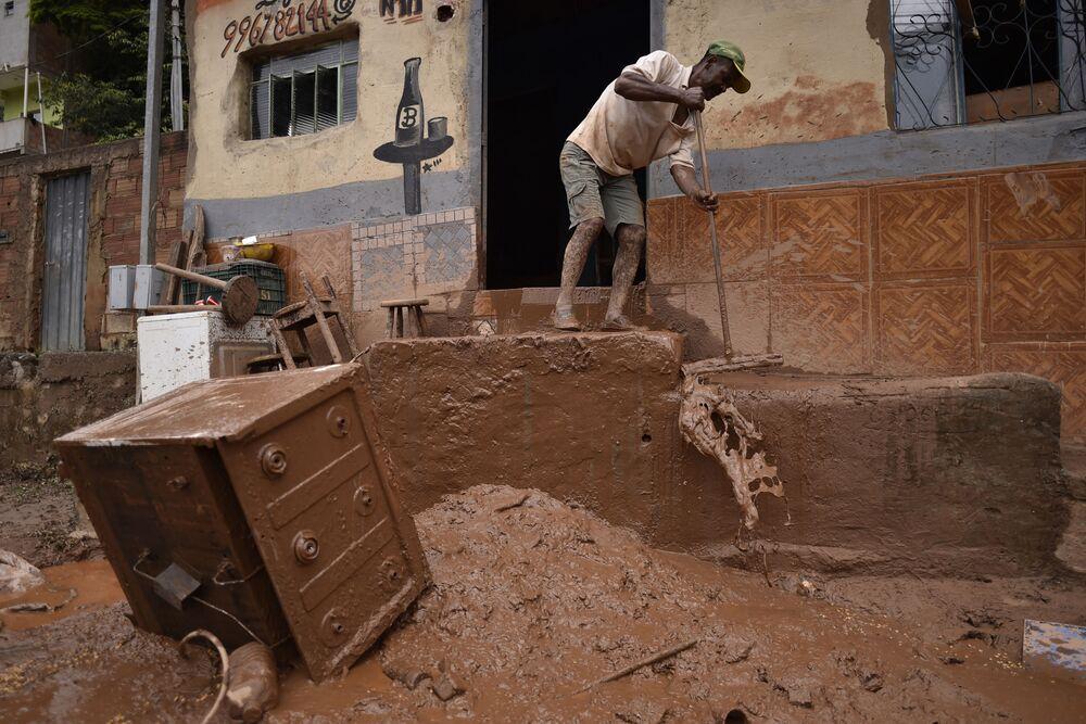 Homem varre lama em casa em Minas Gerais