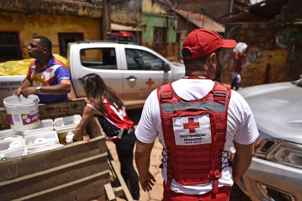 Membros da Cruz Vermelha entregam água e produtos de limpeza para locais em Minas Gerais