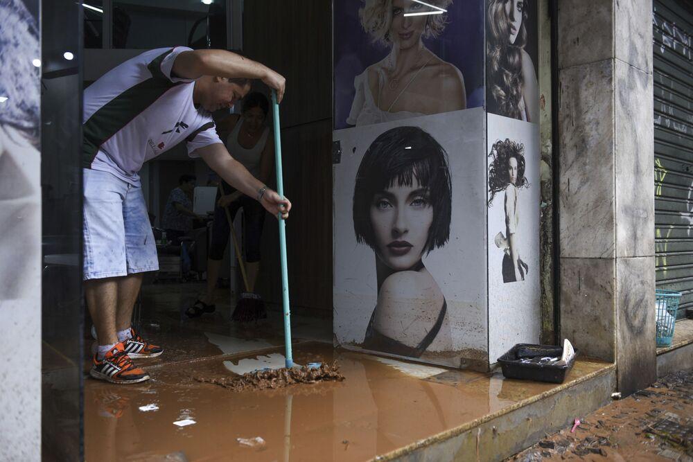 Homem limpa loja alagada durante fortes chuvas em Belo Horizonte