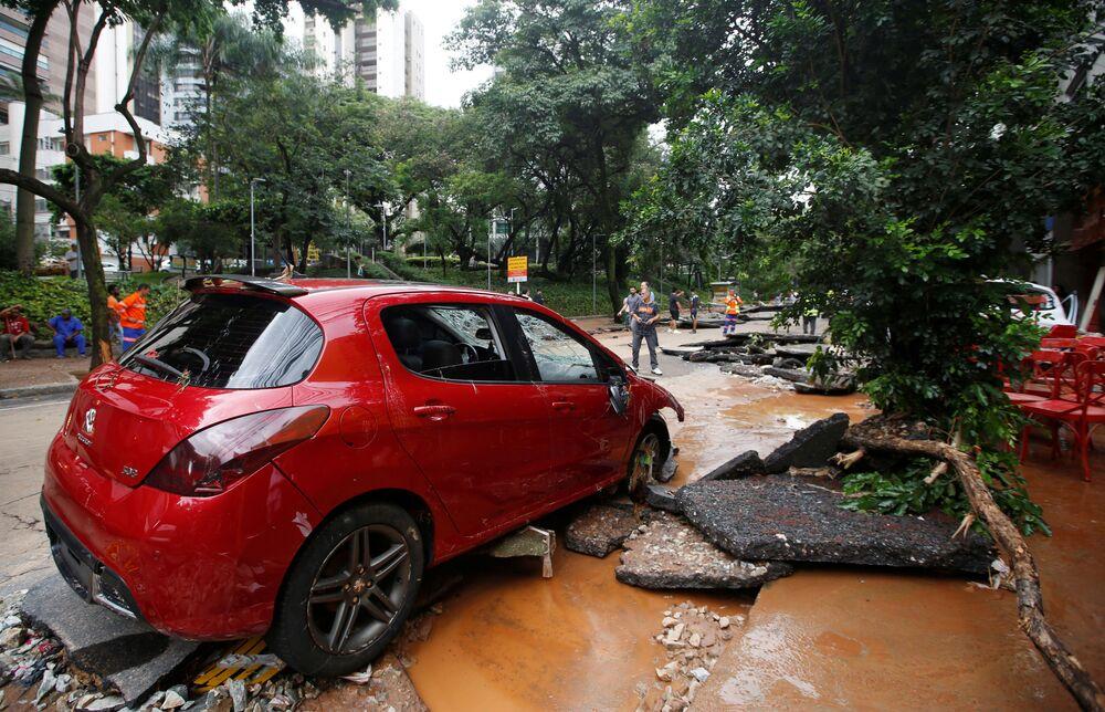 Carro vermelho em meio aos destroços de uma rua em Belo Horizonte