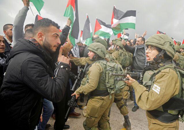 Manifestante palestino discute com soldado israelense durante protesto contra o plano de Trump, em 29 de janeiro de 2020