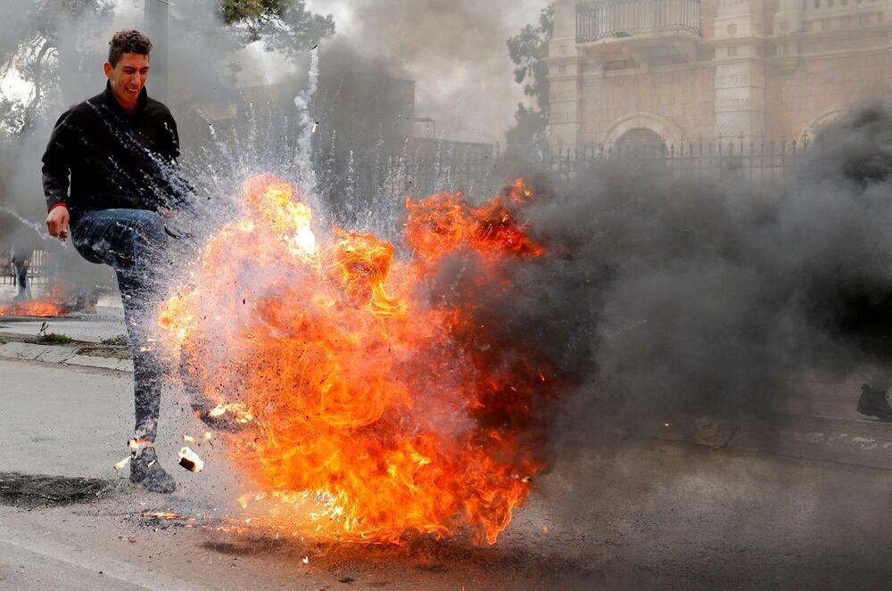Manifestante palestino chuta pneu em chamas durante protesto realizado em Belém contra o plano de Trump