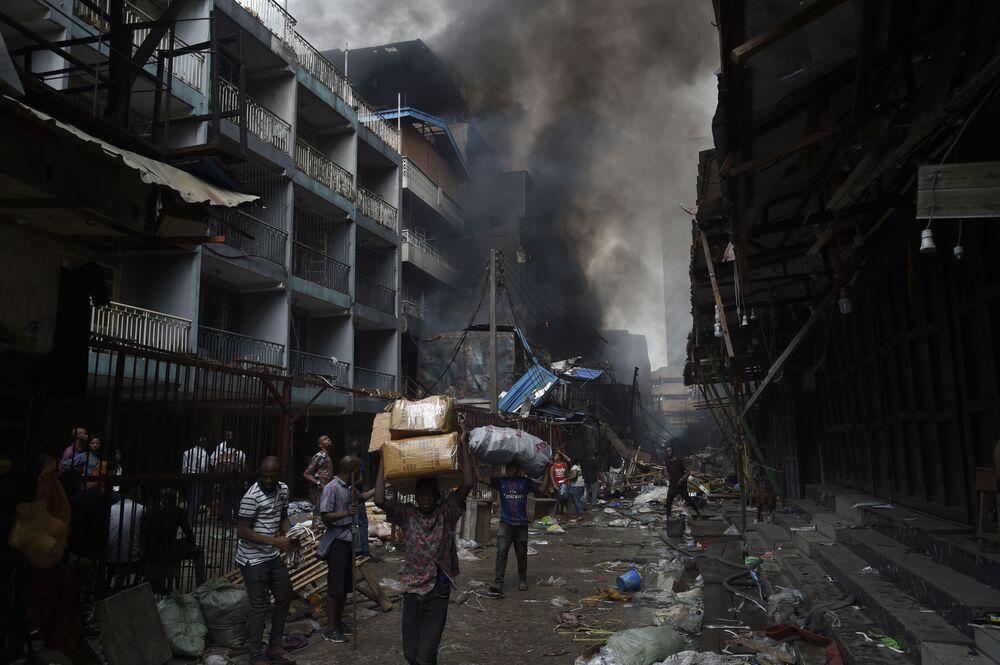 Populares carregam mercadorias que restaram de um incêndio que acometeu parte do mercado de Balogun, na Nigéria