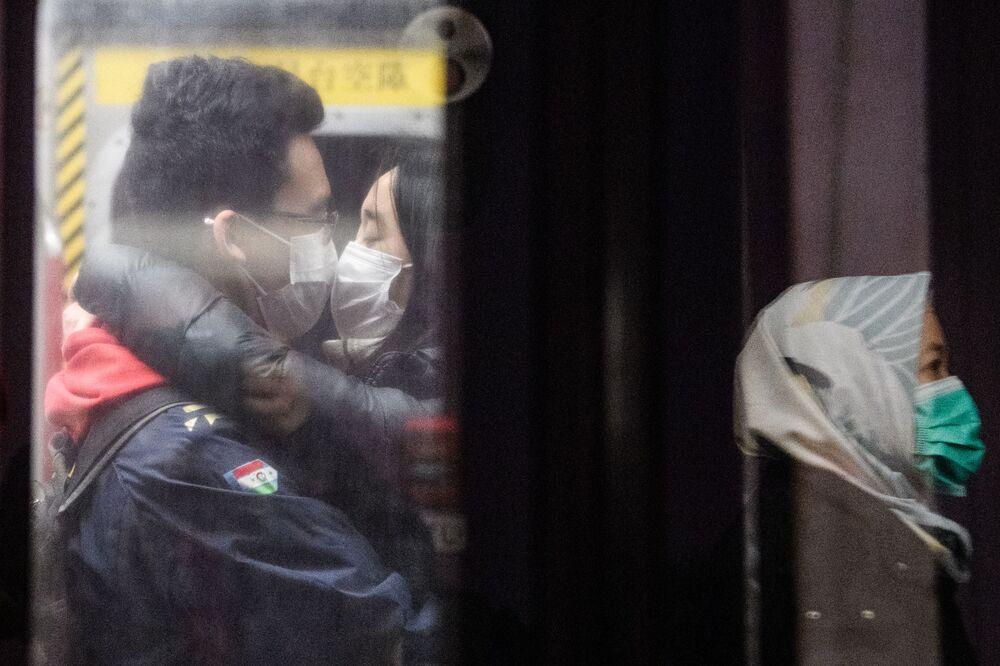 Casal tenta se beijar enquanto usam máscaras no metrô de Hong Kong