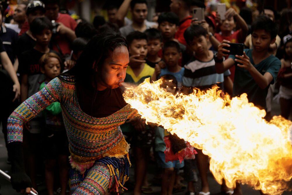 Artista de rua cospe fogo durante celebrações do Ano Novo chinês em Manila, Filipinas