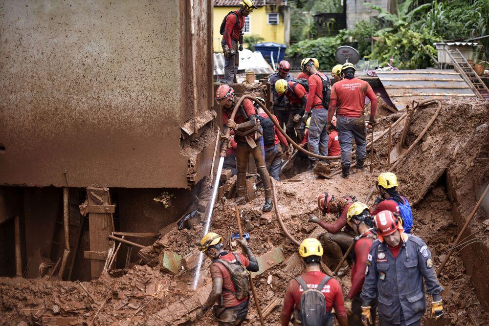 Bombeiros buscam pessoas desaparecidas utilizando técnicas hidráulicas para remover a lama após um deslizamento de terra ocorrer em Belo Horizonte